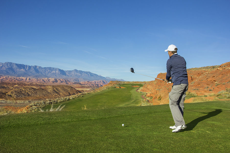 Rear view of a man playing golf on a Sunny day on a beautiful desert golf course in the Southwestern United States